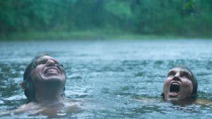 Tina (Eva Melander) och Vore (Eero Milonoff) simmar i en sjö medan det regnar och ropar av glädje.