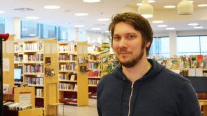 En man står inuti ett bibliotek.