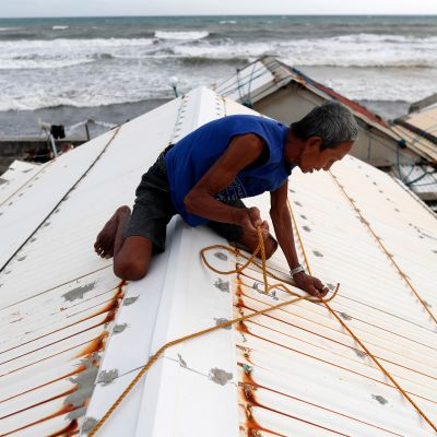 Filippiiniläiset varautuvat taifuunin tuloon vahvistamalla kattoja.