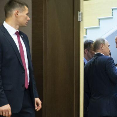 Venäjän presidentti Vladimir Putin ja Turkin presidentti Recep Tayyip Erdoğan keskustelevat kuvan oikeassa laidassa. Vasemmalla etualalla venäläinen henkivartija seisoo oven ulkopuolella.