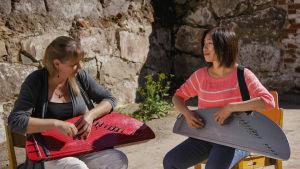 Kaksi naista istuu ulkona tuoleilla kanteleet sylissä, taustalla tiilimuuri