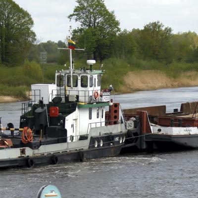 En pråm lastad med Baltikums ny största autotransformator flyter upp för floden Njemen mot Alytus i södra Litauen.