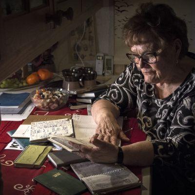 Kokkolalainen eläkeläinen Anja Auvinen selailee kalenteriaan keittiön pöydän äärellä.