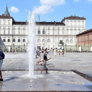 Turister svalkar sig i fontänen på ett torg i Torino i Italien