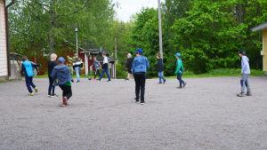 Pojkar i lågstadieåldern spelar fotboll på en skolgård.