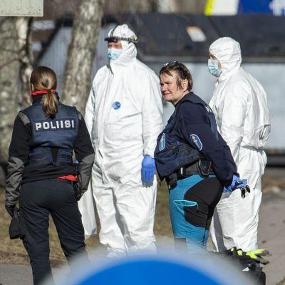 Personer i polisuniform och i skyddsdräkt står bredvid ett hus.