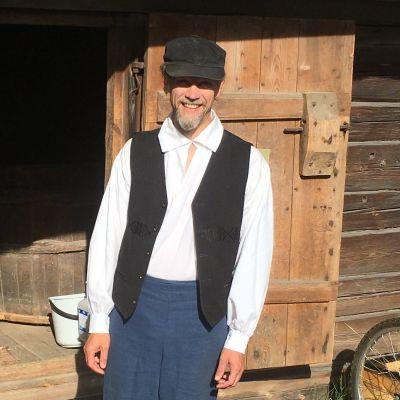 Jouni Sjöblom seisoo Kouvolan Puolakan talomuseon pihassa ja hymyilee kameralle.