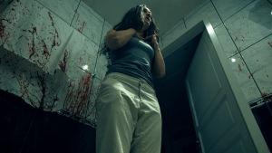 Scen ur skräckfilmen Lust där den kvinnliga huvudrollsinnehavaren står i en svagt belyst badrumsmiljö, med stora blodfläckar på kakelväggarna.