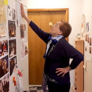 vanha nainen lukee seinältä ohjeita huoneessaan