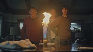 Steve, Annie och Peter står vid ett bord och ser förskräckta ut då ett ljus på bordet flammar upp med en enorm låga.