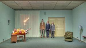 Kuvassa on kolme miestä puku päällä, he nojaavat takaseinään. Kuvan vasemmassa laidassa on nainen keltaisessa mekossa pöydällä pitkällään, hän tekee jaloillaan jumppaliikettä. Rooleissa Elina Knihtilä, Tommi Korpela, Ylermi Rajamaa ja Aleksinja Lommi.
