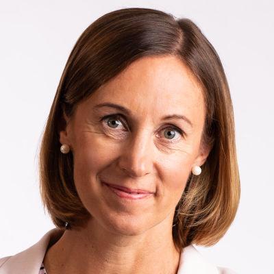En kvinna, Jessica Ålgars, står framför en vit vägg. Hon tittar in i kameran och ler.