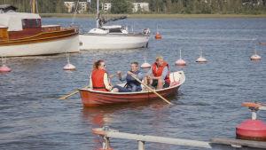 Kolme ihmistä soutuveneen kyydissä, yksi soutaa laiturissa olevien veneiden ohitse.