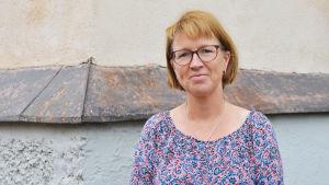 En medelålders kvinna i blommig blus står framför ett gulrappat hus. Hon ser in i kameran och ler.