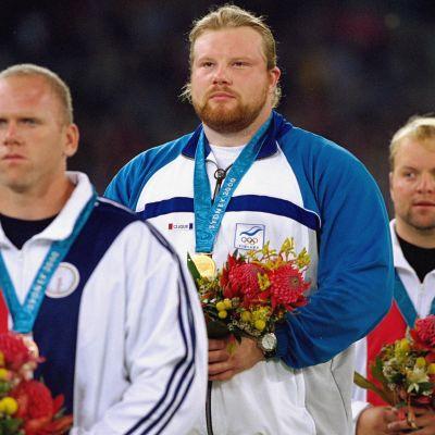 Arsi Harju (kesk.) voitti olympiakultaa Sydneyssä tuloksella 21,29. Hopeaa sai Yhdysvaltain Adam Nelson (taka-alalla), 21,21, ja pronssia hänen maanmiehensä John Godina (edessä), 21,20.