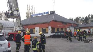 Brandmän står samlade kring ett hus som har skylten Hotel Polaris på taket. Ingen brand, inga lågor, ingen rök syns på bilden.