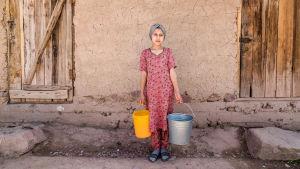 Tadzhikistanilainen tyttö vesiämpärien kanssa.