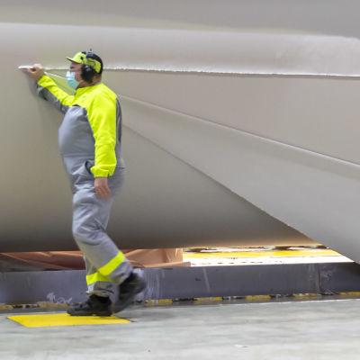 Tre pappersarbetare i neongula och gråa arbetskläder skär bort en extra bit på en ca 10 meter lång pappersrulle