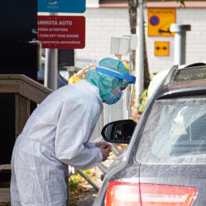 Hoitaja puhuu autossa olevalle asiakkaalle Eksoten drive-in koronanäytteenottopisteessä Lappeenrannassa.