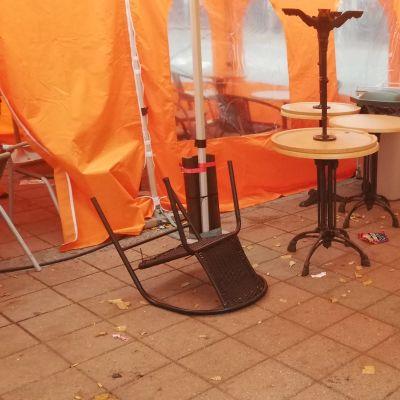 Tuoleja kumollaan torikahvilan teltassa