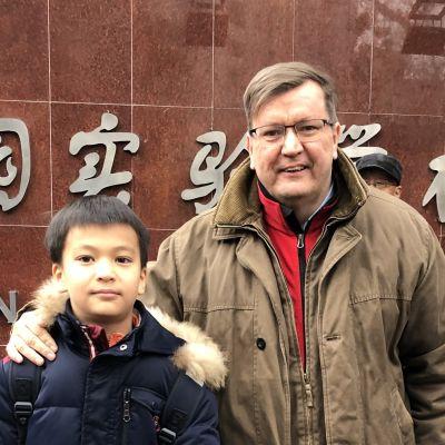 En västerländsk man med glasögon står med armen om en kinesisk pojke. De ler mot kameran.