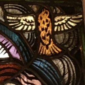 Den helige anden i form av en duva på glaskonstfönster i Brändö kyrka.