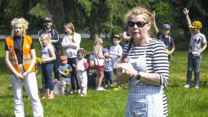 Anneli Bäckström står på en gräsmatta i lekparken Intia i Forsby och leder en grupp barn.