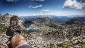 Peter Jofs lutar sig tillbaka i bergen. På bilden syns hans ben och i bakgrunden en mäktig vy av bergskedjan Pyrenéerna.