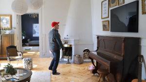 Man med röd keps och smårutig jacka ser sig omkring i ett stort vardagsrum