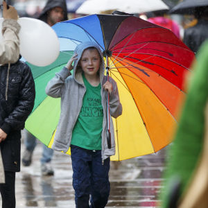 En pojke håller i ett regnbågsfärgat paraply medan han går ute i regnet.