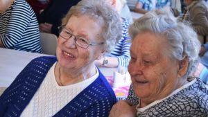 Två äldre kvinnor sitter i en publik och ler.