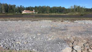 Stenvall mot Infjärden. Bakom stenvallen syns den jordmassa som kommit upp till ytan. Först efter den kommer sjön.