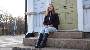 En ung kvinna i jeans och svart jacka sitter på en stentrappa utanför ett blått trähus. Hon tittar in i kameran och ler.
