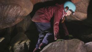 Kvinna i blå hjälm och pannlampa går hukad mellan stenar inuti en grotta.