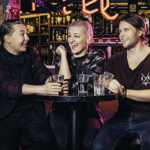 YleX:n iltapäiväohjelman uudet juontajat Mika Parikka, Jenni Poikelus ja Jere Pehkonen pöydän ääressä.