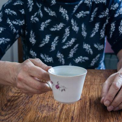 Vanhempi henkilö, joka pitelee pöydän ääressä valkoista kahvikuppia.