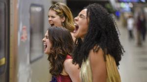 kolme nuorta naista huutavat, metro menee ohi.