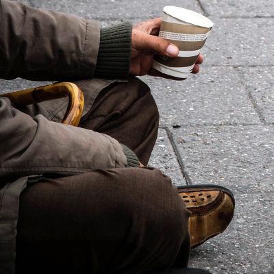 En bildsättningsbild där kroppen på en person som håller en pappmugg i handen syns. Hen sitter på grå trattoar.