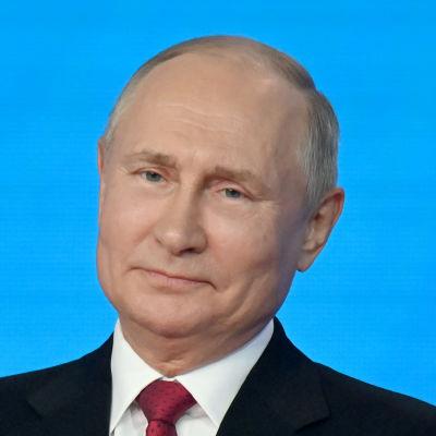 Närbild av Vladimir Putin klädd i kostym. Han ler medan han lutar huvudet något åt sidan. Han tittar inte in i kameran. I bakgrunden syns en ljusblå vägg.
