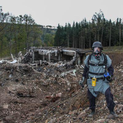 Suojapukuun, kaasunaamariin ja kypärään pukeutunut mies seisoo räjähtäneen näköisessä maisemassa tuhoutuneen betonisen rakennelman edessä.Taustalla näkyy metsämaisemaa.