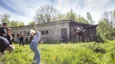 Människor dansar på en äng och i bakgrunden spelar en man musik.