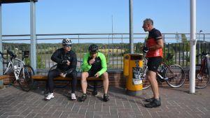Tre cyklister har matpaus i Gammelby. De sitter utomhus på en bänk.
