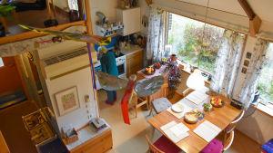 Kati står i köket och lagar i ordning. Bilden är tagen från loftet och i vänstra sidan skymtar ett par drakar som hänger i taket.