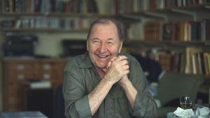 Roy Andersson sitter skrattande vid sitt arbetsbord med bokyllor vi bakgrunden.