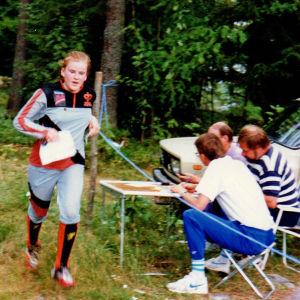 Suunnistaja Anne Leinonen ohittanut kartta kädessään maalin, jossa kolme miestä istuu puutarhatuoleissa ja kirjaa tuloksen.