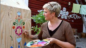 Camilla målar ett litet hus.