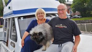 En kvinna, en man och en hund sitter utanpå en blåvit båt i Borgå gästhamn.