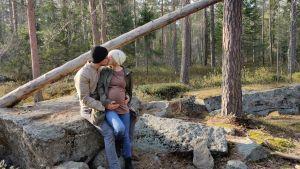 En man och en gravid kvinna kramas och pussas i skogen. De lutar sig mot en sten.