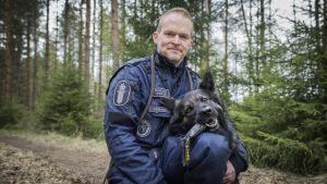 Polis Ari Pynssi sitter på huk på en skogsväg tillsammans med polishunden Cama