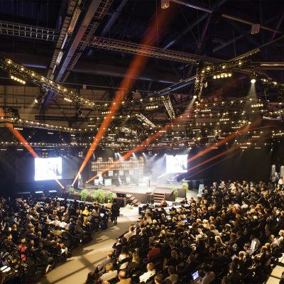 Massor med människor sitter, står och följer med konferensen Slush 2014 i en stor arena med färggranna strålkastare.
